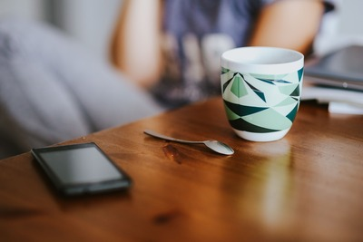 kaboompics_Black smartphone and a mug