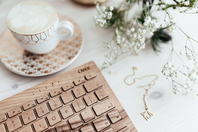 kaboompics_Wooden keyboard, coffee and golden jewellery